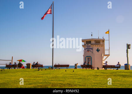 Laguna Beach, California - October 9, 2018: Lifeguard tower and flagpole with American Flag with grassy foreground at Laguna beach on this date - Stock Photo