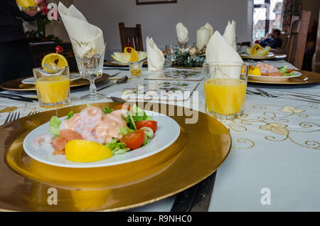 Starters of prawn cocktail and melon along with glasses of orange juice on a dinign table ready for eating a meal. - Stock Photo