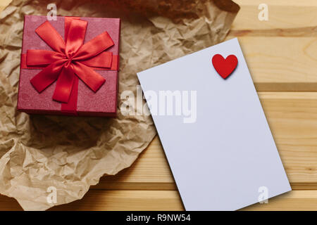 Red box with a gift and next to a white blank sheet for text with a heart on a wooden surface. Festive concept for Valentine's Day or Women's Day or Mother's Day. - Stock Photo