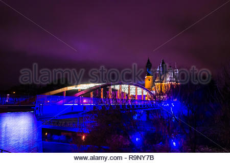 Poznan, Poland - December 26, 2018: Jordan bridge with Christmas lights over the Warta river by night. Cathedral on the Ostrow Tumski in the background.  - Stock Photo