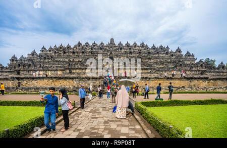 visitors at Candi Borobudur, the 9th century Buddhist temple in Central Java, Indonesia - Stock Photo