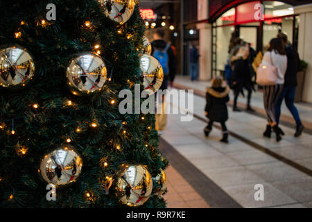 A Christmas tree with golden baubles and Christmas lights in a shopping mall with Christmas shoppers carrying shopping bags in the background - Stock Photo