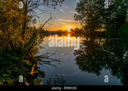 Colorful sunset over a lake in Holland in autumn. Scenic view of a lake with trees at sunset near Gouda, The Netherlands. - Stock Photo