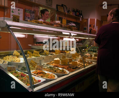 Woman buying food at a streetside food counter, Old Town Genoa, Italy. People not identified or released. - Stock Photo
