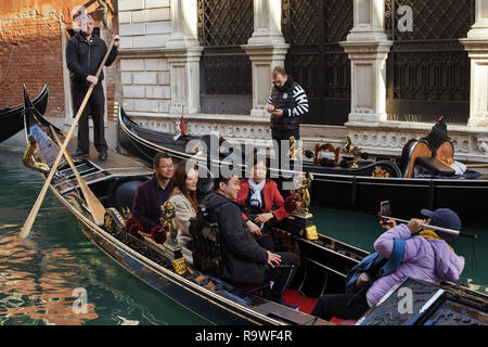 Asian tourists attend the gondola tour in Venice, Italy. - Stock Photo