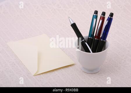 Yellow envelope,  a plastic pen on paper - Stock Photo