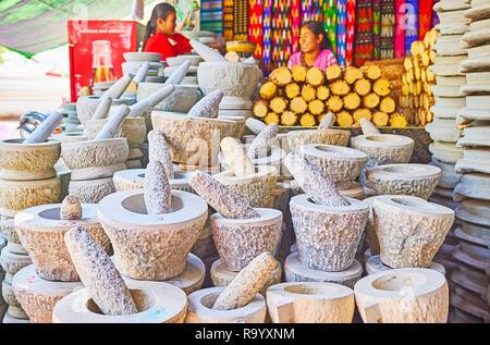 SAGAING, MYANMAR - FEBRUARY 21, 2018: Stall of Kaunghmudaw Pagoda market with kyauk pyin mortars and pestles for grinding thanaka and producing tradit - Stock Photo
