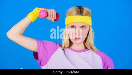 Beginner dumbbell exercises. Ultimate upper body workout for women. Fitness concept. Girl exercising with dumbbell. Workout with dumbbell. Fitness instructor hold little dumbbell blue background. - Stock Photo