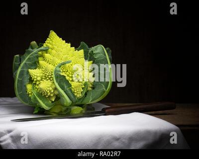 Romanesque aka romanesco broccoli with white cloth and knife. Still life, food. Broccoflower. - Stock Photo