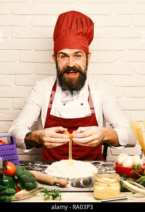 Cook with cheerful face in burgundy uniform sit by table with vegetables and kitchenware. Professional cookery concept. Man with beard breaks egg into flour on white brick background. Chef makes dough - Stock Photo