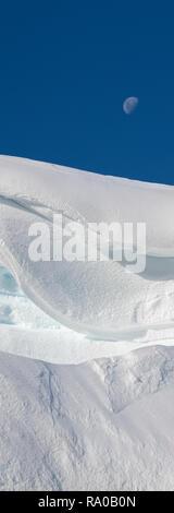 Antarctica, Antarctic peninsula, Gerlach Straight, Wilhelmina Bay in the Enterprise Island area. Moon over snowy mountain edge. - Stock Photo