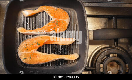 cooking raw salmon on the grill stove background horizontal - Stock Photo