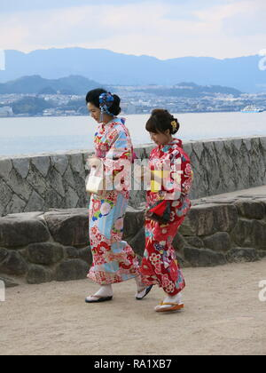 Two young women in traditional Japanese kimonos walk along the seafront on Miyajima Island, Japan; both holding bags and mobile phones - Stock Photo