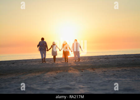 Happy Loving Family Holding Hands and Embracing While Facing the Bright Orange Yellow Sunset over the Ocean at the Florida Beach Horizon - Stock Photo