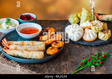 Giant king prawns and selection of mini Chinese dumplings with sweet chili and yogurt dipping sauces. Party food idea. - Stock Photo