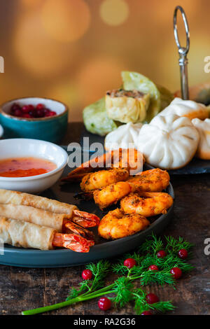 Giant king prawns and selection of mini Chinese dumplings with sweet chili dipping sauce. Party food idea. - Stock Photo