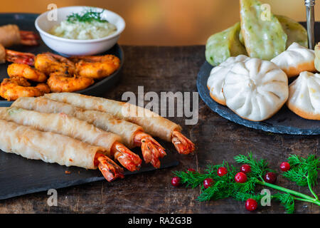 Giant king prawns and selection of mini Chinese dumplings with yogurt dipping sauces. Party food idea. - Stock Photo