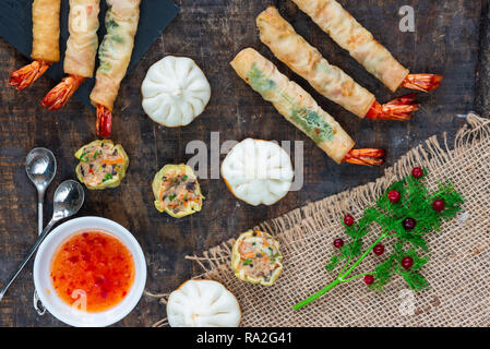 Giant king prawns and selection of mini Chinese dumplings with sweet chili dipping sauce. Party food idea. Top view. - Stock Photo