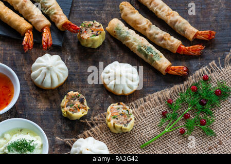 Giant king prawns and selection of mini Chinese dumplings with sweet chili and yogurt dipping sauces. Party food idea. Top view. - Stock Photo