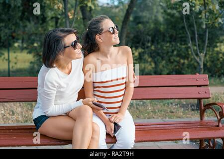Communication between parent and child. Mom and daughter teenager talking and laughing while sitting on the bench in the park. - Stock Photo