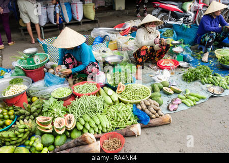 Vietnamese women stallholders wearing conical hats displaying fresh local fruit and vegetables for sale in a market. Can Tho Mekong Delta Vietnam Asia - Stock Photo