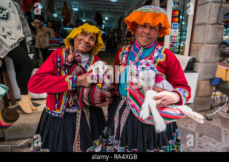 Peruvian women in traditional clothing standing smiling at the camera clutching young lambs in their arms - Stock Photo