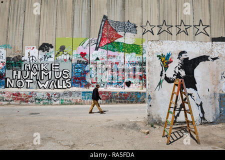 A Palestinian man walking around the infamous Israeli West Bank barrier in Bethlehem. West Bank. Palestine. - Stock Photo