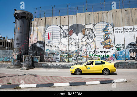 Palestinian yellow cab around the infamous Israeli West Bank barrier in Bethlehem. West Bank. Plaestine - Stock Photo