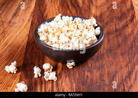 Salt popcorn on the wooden table. Popcorn in a stone bowl. Watching a movie with popcorn. Copy space. Pop corn. - Stock Photo