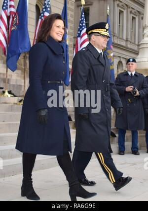 Michigan Gov.-elect Gretchen Whitmer, left walks with Brig. Gen. Paul Rogers as they walk out to the dais for the swearing in inauguration ceremony at the State Capitol January 1, 2019 in Lansing, Michigan. Whitmer, a Democrat was sworn in as the 49th governor of Michigan. - Stock Photo