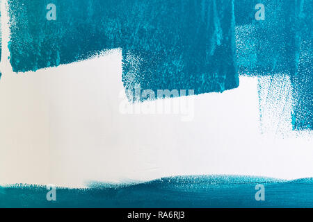 White wall being painted in blue or aqua or teal color. Background with copy space. - Stock Photo