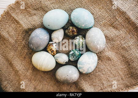Stylish easter eggs  in circle on rustic fabric on white wooden background, flat lay. Modern easter eggs painted with natural dye in blue and grey mar - Stock Photo