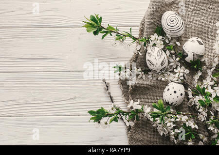 modern easter flat lay. stylish easter eggs on rustic white wooden background with fresh spring flowers top view. space for text. stylish painted eggs - Stock Photo