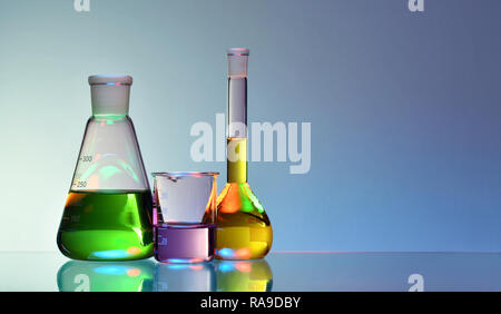 Laboratory glassware with colorful liquids and chemicals on blue background - Stock Photo