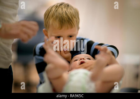 Little boy curiously looking at his baby brother lying on his back. - Stock Photo