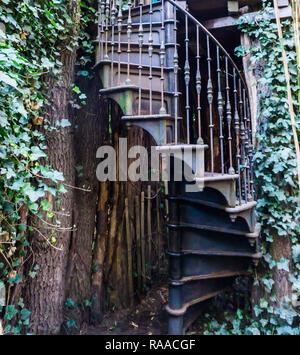 vintage iron spiral staircase in a garden, outdoor architecture - Stock Photo