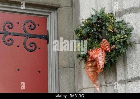 Traditional natural green Christmas wreath hanging next to the door of a church - Stock Photo