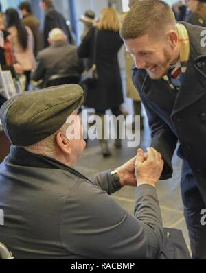 Former U.S. Army Spc. Kenneth Stumpf, Medal of Honor recipient and retired U.S. Marine Corps Cpl. William Kyle Carpenter, Medal of Honor recipient, exchange coins during a traditional Inaugural Day Medal of Honor breakfast held at the Reserve Officers Association headquarters in Washington D.C., January 20, 2017. - Stock Photo