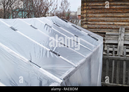 Greenhouse for growing vegetables in the garden. Covered with polyethylene film to preserve moisture and heat. On the background of wooden wall - Stock Photo