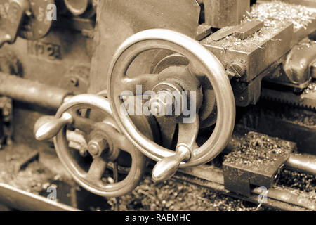 Close-up of the control adjustment wheels on an old industrial lathe with toning - Stock Photo