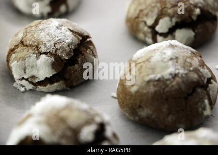 Step-by-Step. Baking homemade chocolate crinkle cookies with powdered sugar icing. Hot fresh cookies on parchment paper - Stock Photo