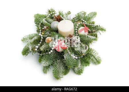 Christmas decoration consisting of fir twigs, shiny balls, cones around the candle, covered with snow on a white background - Stock Photo