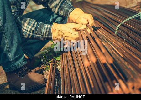 Construction Industry. Steel Reinforcement Bars on a Ground. Contractors Hands on the Steel Elements. - Stock Photo