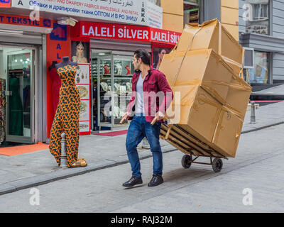Istanbul, Turkey, February 24, 2015: Man pulling boxes on a trolley, down a street in Laleli. - Stock Photo
