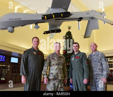 U.S. Air Force Col. Julian Cheater, 432nd Wing/432nd Air Expeditionary Wing commander (left), U.S. Army Lt. Gen. Paul Funk, III Armored Corps and Fort Hood, Texas, commanding general (second from the left), U.S. Air Force Col. Jim,  432nd  WG/432nd AEW vice commander (second from the right), and Chief Master Sgt. Jamie, 432nd  WG/432nd AEW command chief (right), stand under an MQ-1 Predator at Creech Air Force Base, Nevada, Dec. 10, 2018. Funk made a visit to Creech to thank the Remotely Piloted Aircraft Airmen who kept the Soldiers he led safe during Operation Inherent Resolve. - Stock Photo