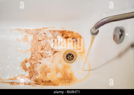 Dirty brown running water falling into a white sink from tap. Environmental pollution concept - Stock Photo
