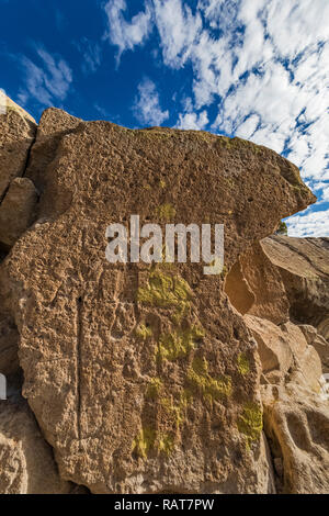 Petroglyphs, including human figures, carved into sandstone by Ancestral Puebloan People at the Tsankawi Prehistoric Sites in Bandelier National Monum - Stock Photo