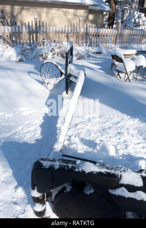 A winterized basketball hoop prone in snow storage waiting for spring. St Paul Minnesota MN USA - Stock Photo