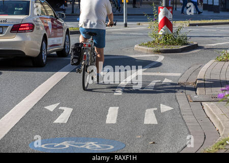 Inner-city bike path, especially marked cycle paths, bicycle lanes, for cyclists, in Essen, at a traffic light junction, Germany - Stock Photo