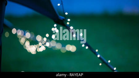 Bokeh Fairy Lights on a string hanging from an outdoor Bedouin tent for corporate event - Stock Photo